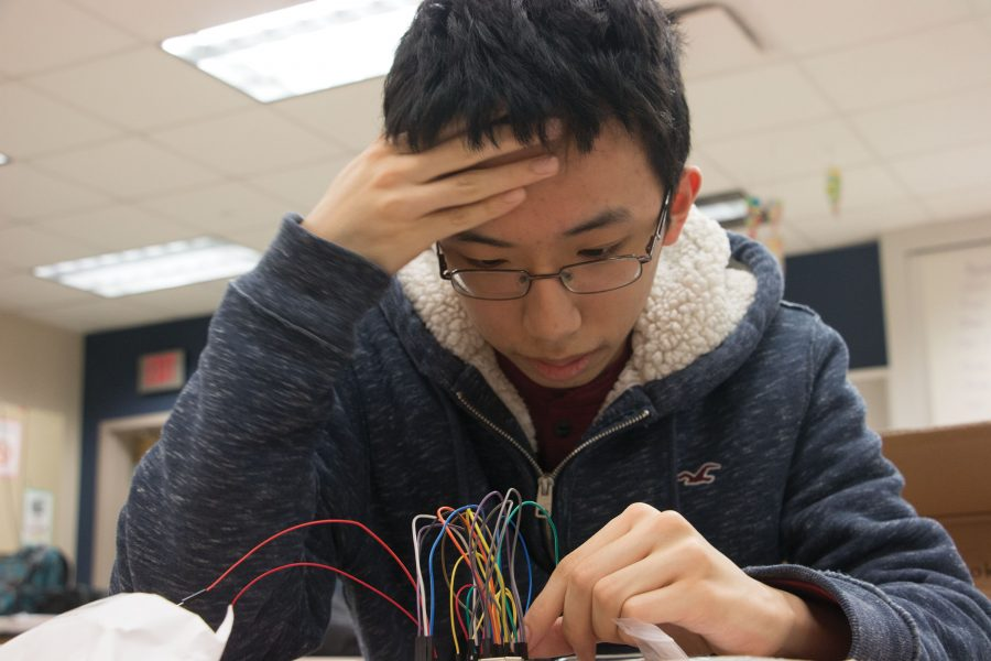 """READY, SET , INVENT: Sophomore and InvenTeam member Lifan """"Kyle"""" Zheng wires a device for the Carmel InvenTeam. The device detects impulses and signals that are meant to mimic the human body system during seizures and other abnormalities."""