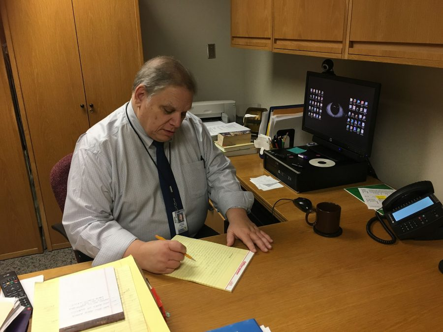 A.C.T. coach John Shearin sits at his desk, looking at his computer, with the team's trophy on display next to him. He said he thinks the team is playing very well this season, and is saddened that some of his top players are seniors and will no longer be on the team next year.