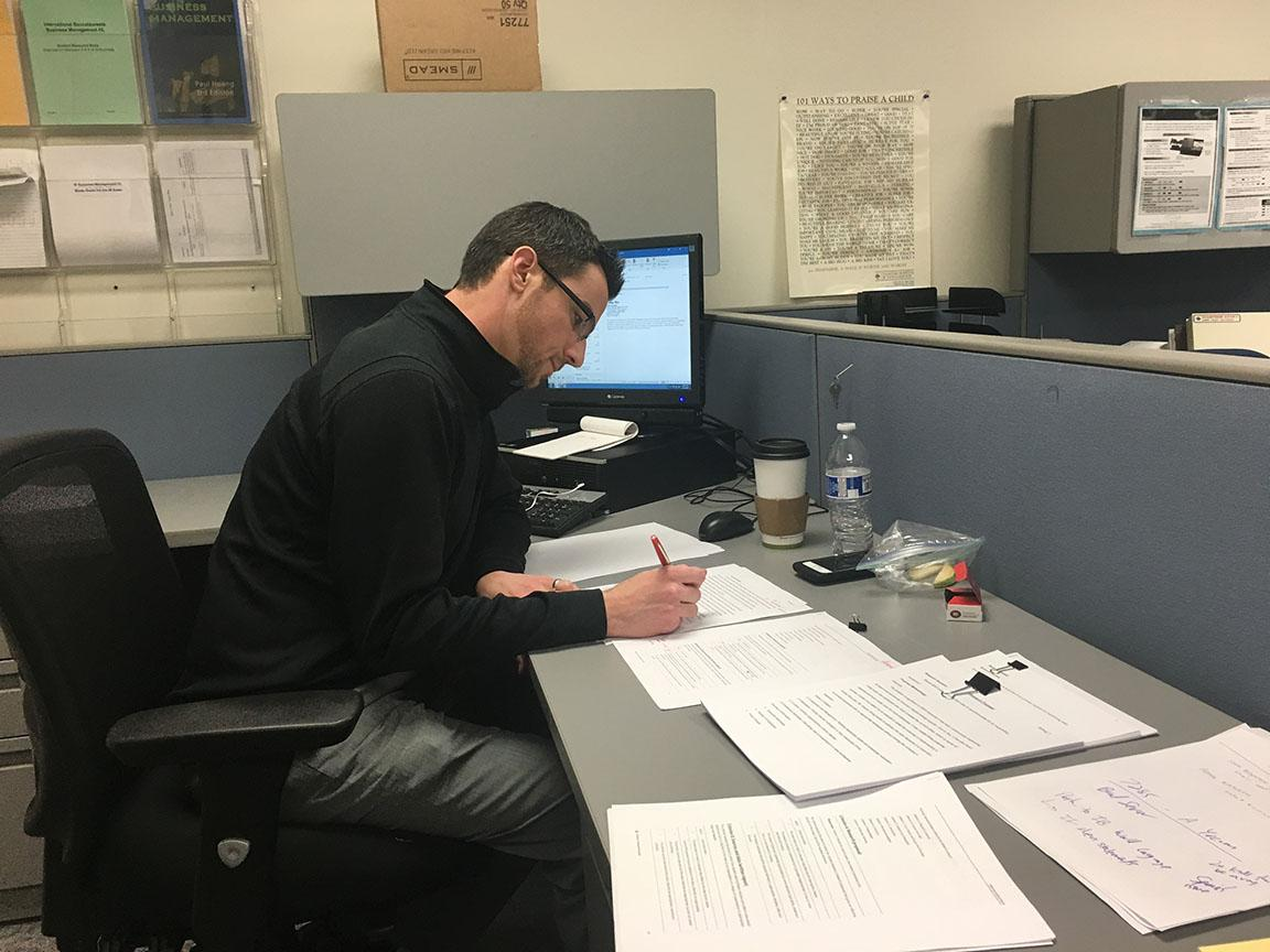 Chard Reid, CHS DECA leader and business teacher, looks over DECA papers in his office. Reid has been overseeing the entire DECA Junior project since it's conception in November.