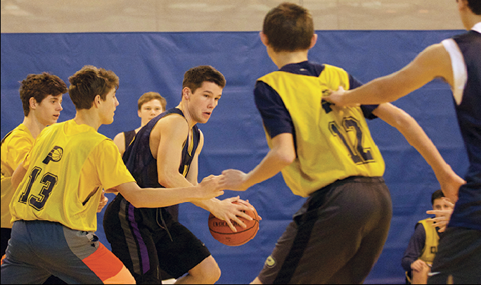 """FIND THE OPEN MAN: Jacob """"Jake"""" Waples (center), Dads Club player and senior, passes the ball during a Dads Club game. Waples said the games are intense but also a lot of fun while he plays with friends in a competitive setting."""