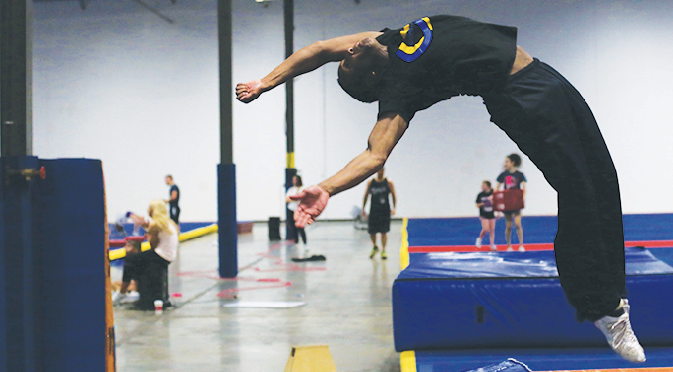 HIGH FLYER Gymnast and senior George Schrader flips in the air during his practice. Schrader participates in tumbling and different cheerleading events. Throughout the week Schrader does both strength training and different practices with stunts and routines.