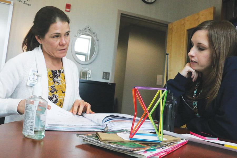 MEDIATING LEADERS:  Social worker Abby Cartwright-Brattain (left) and Head of Special Services Lacey Grabek flip through a student survey binder during their break. They also discussed upcoming counseling events later on.