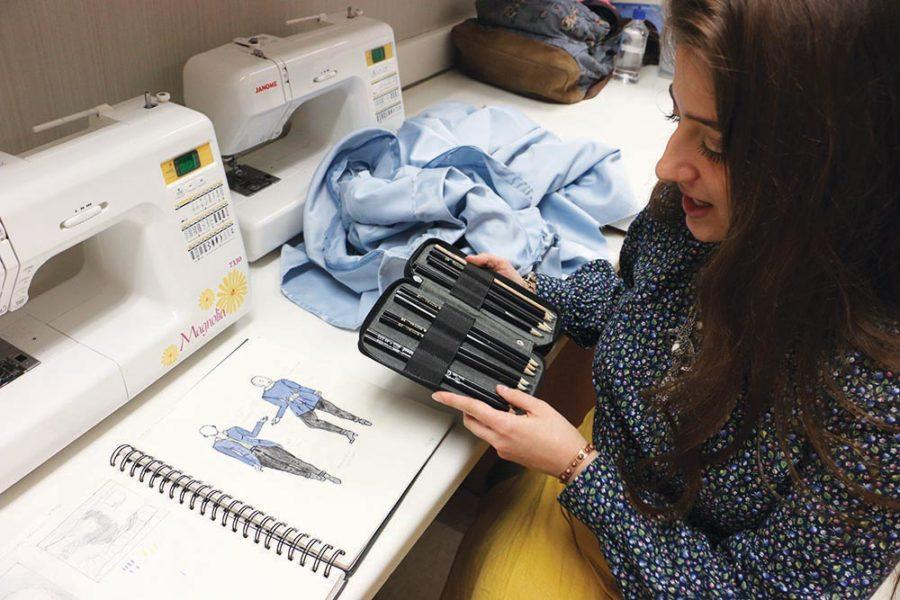 Meeker opens her drawing pencil case and looks at clothing designs in her sketchbook.