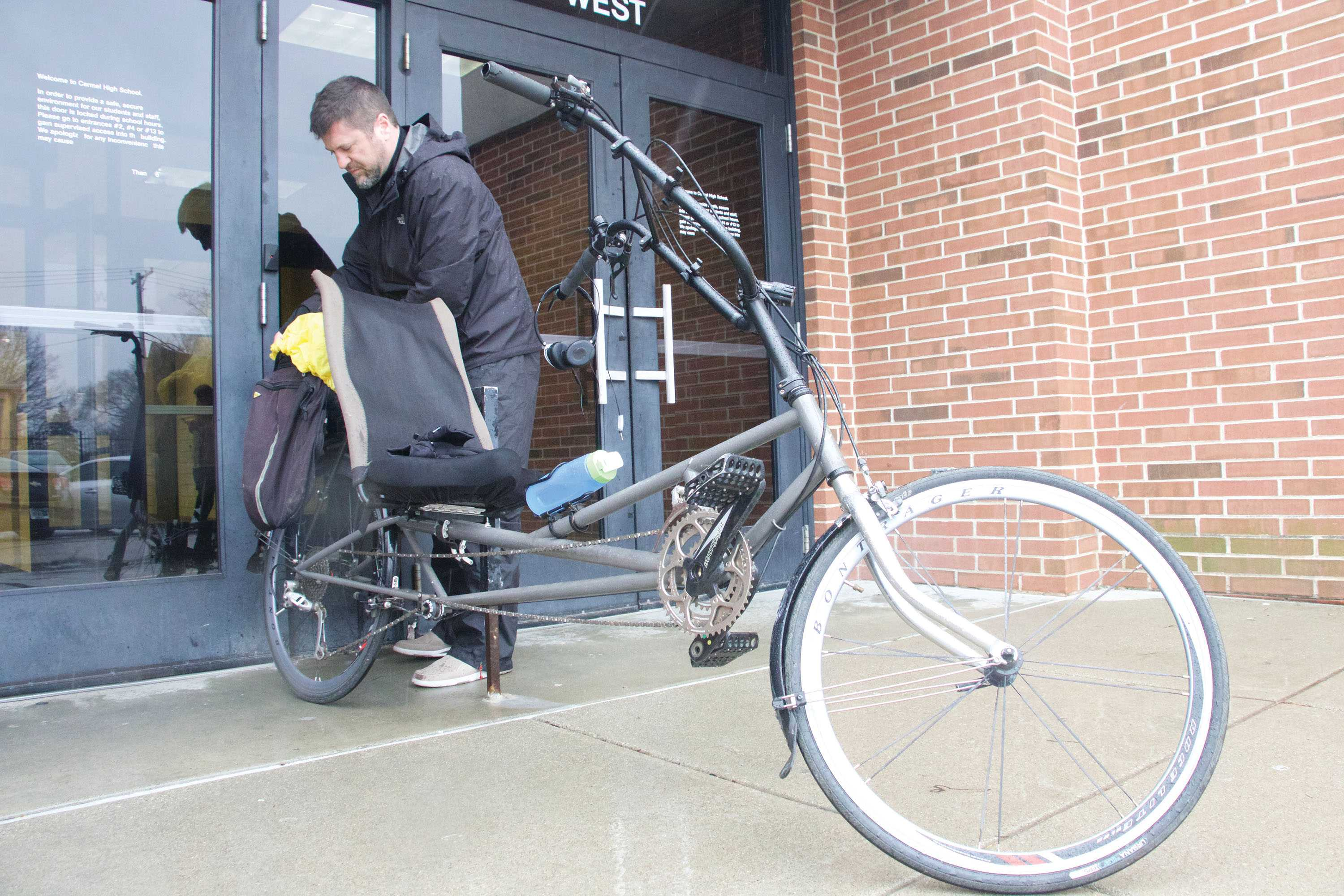Photography teacher Kevin Daly prepares his bike before commuting home after school. Daly said he supports the addition of new bike paths and trails in Carmel, especially because he bikes 22 miles to and from CHS on a daily basis.