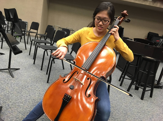 "Selin Oh, Camerata cellist and sophomore, practices her cello in the orchestra room after school. Oh said Camerata members will separately be playing ""Serenade for String Orchestra, Op. 48"" by Pyotr Ilyich Tchaikovsky in addition to performing with the Ambassadors."