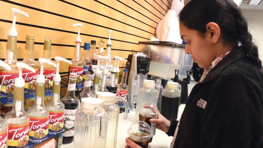 Junior Rithika Chari makes coffee for café customers during SRT. Seketa said in order to expand the café, they will take down the wall in front of Chari and extend it to the business classrooms.
