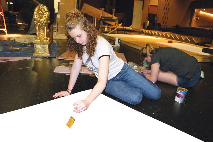 Phoebe Kane, technical crew member and senior, paints props on stage.