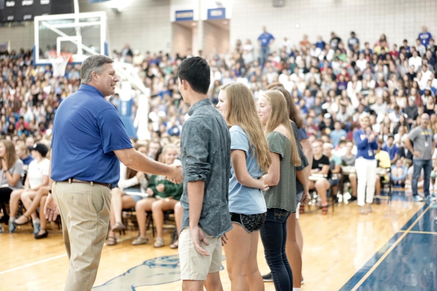 Principal Tom Harmas shakes hands with the 2017-2018 drum majors at the back-to-school convocation. Harmas plans to implement administrator walk-ins this semester.