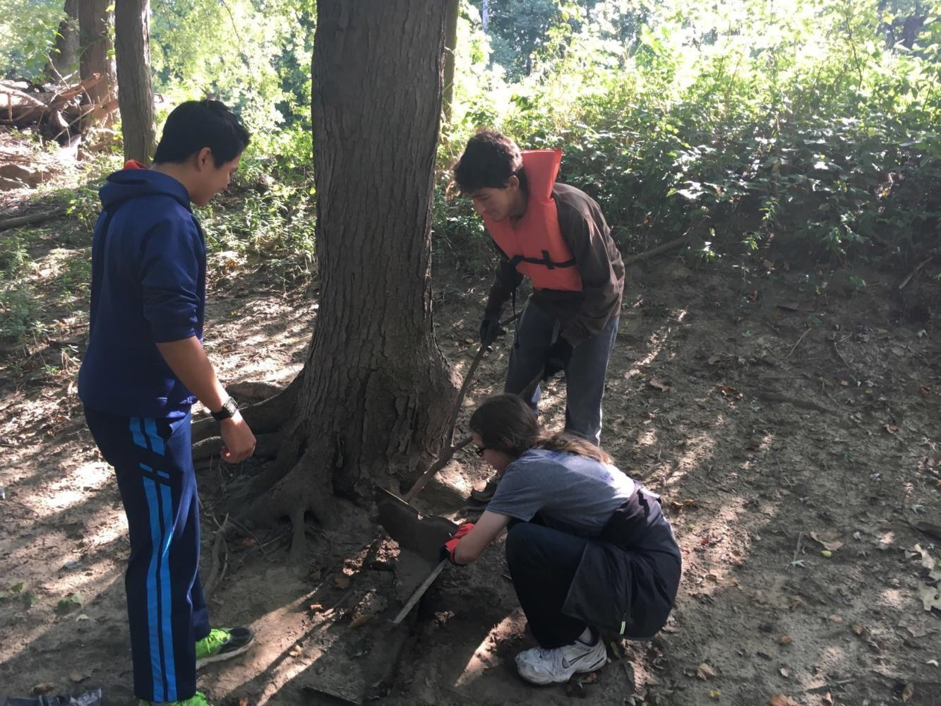 LOCAL IMPACT: Sophomores Kian Robinson, Yannik Singh and freshman Brian Yuan participate in the White River Cleanup. Robinson said that information at the conference should be more pertinent to what people can do in their everyday lives to have a greener impact.