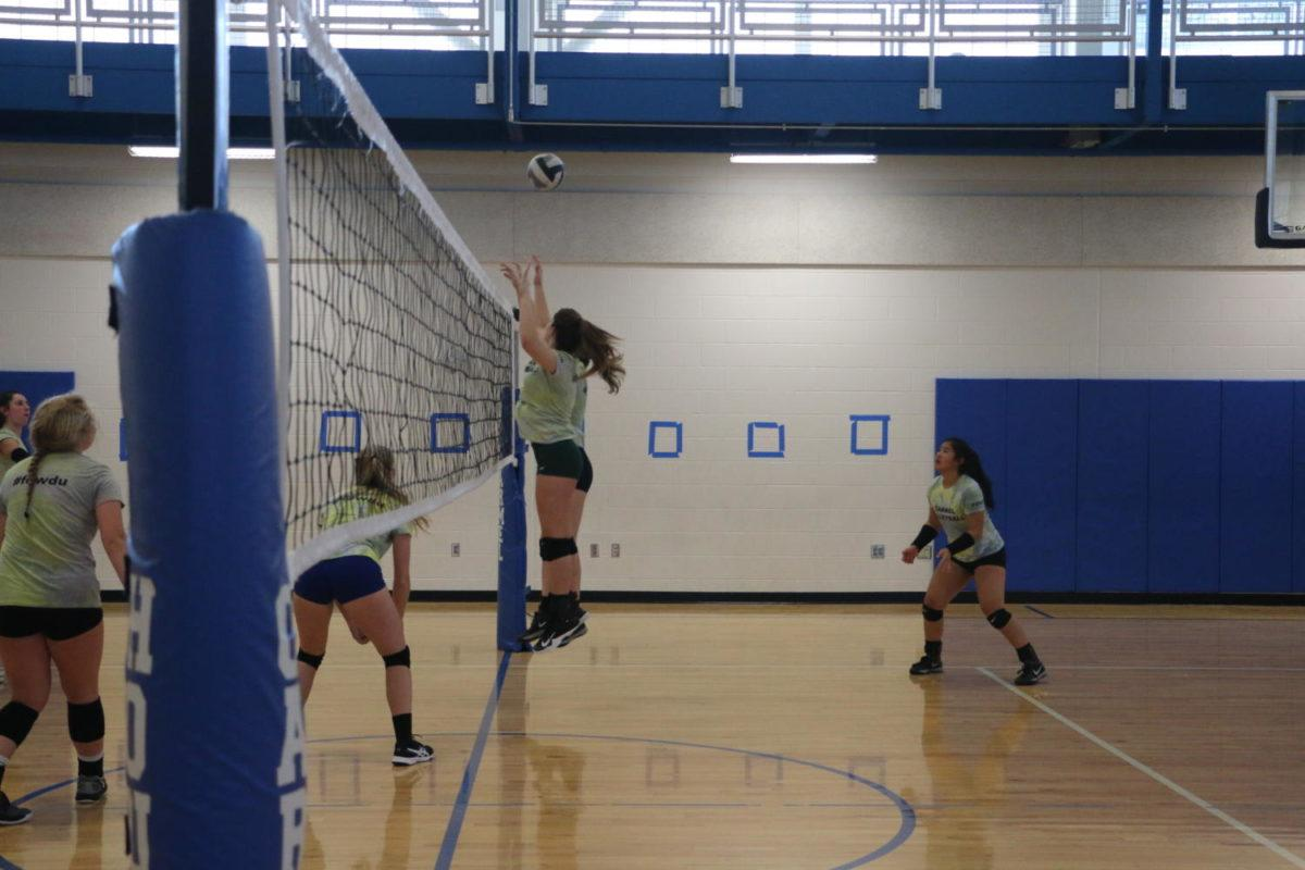 In the middle of a scrimmaging drill, player and junior Yara Batista and player and senior Kailey Akins jump to block a ball coming over the net.  The other players on both sides of the court were practicing a skill called covering, which is when the players stand closer to the net in order to pick up a ball that is missed by one of their teammates.