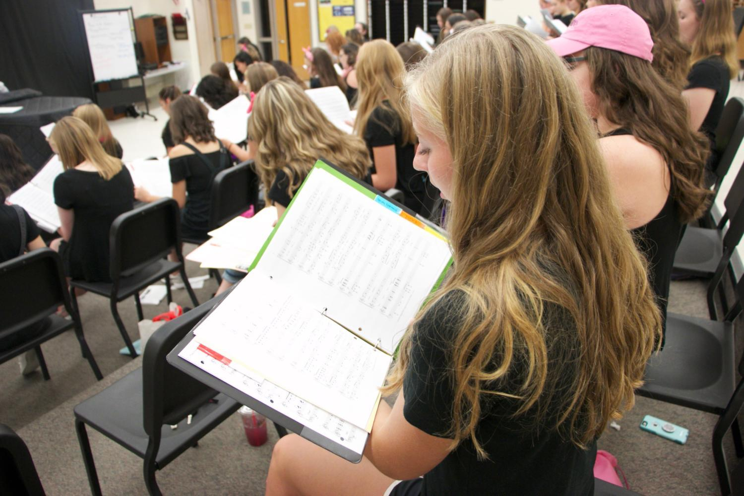 Junior Julia Schmitz looks down at her music at an Accents rehearsal. This rehearsal was in preparation for the upcoming fall concert on Oct. 4.