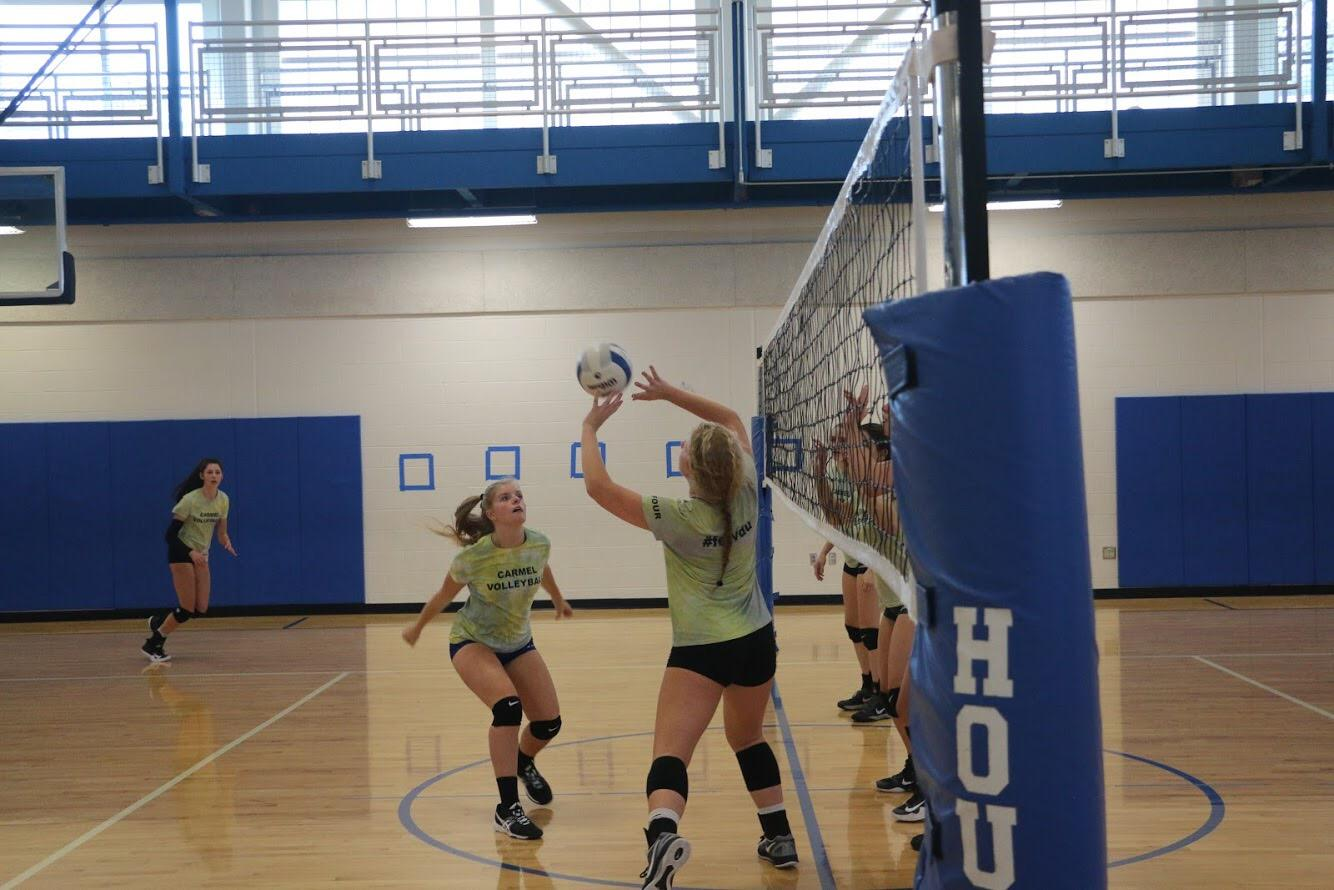 Caption: Setter and junior Lauren Vanremortal sets the ball to Macy Berglund, middle hitter and junior, in order to win the point. The team was scrimmaging each other, but they were specifically working on their offense rather than defense.