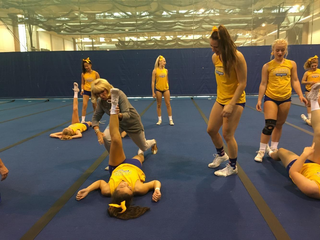 Head Coach Lisa Knipp shows the team a new stretch before starting practice. Junior cheerleader McKenna Abbey waits to the side to do it to her stretching partner.