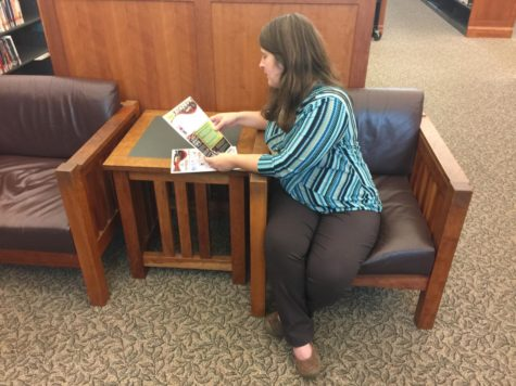 Jamie Beckman, Young Adult Section Librarian, corrects a flyer for the library's events. The volunteering applications for the library are now open.