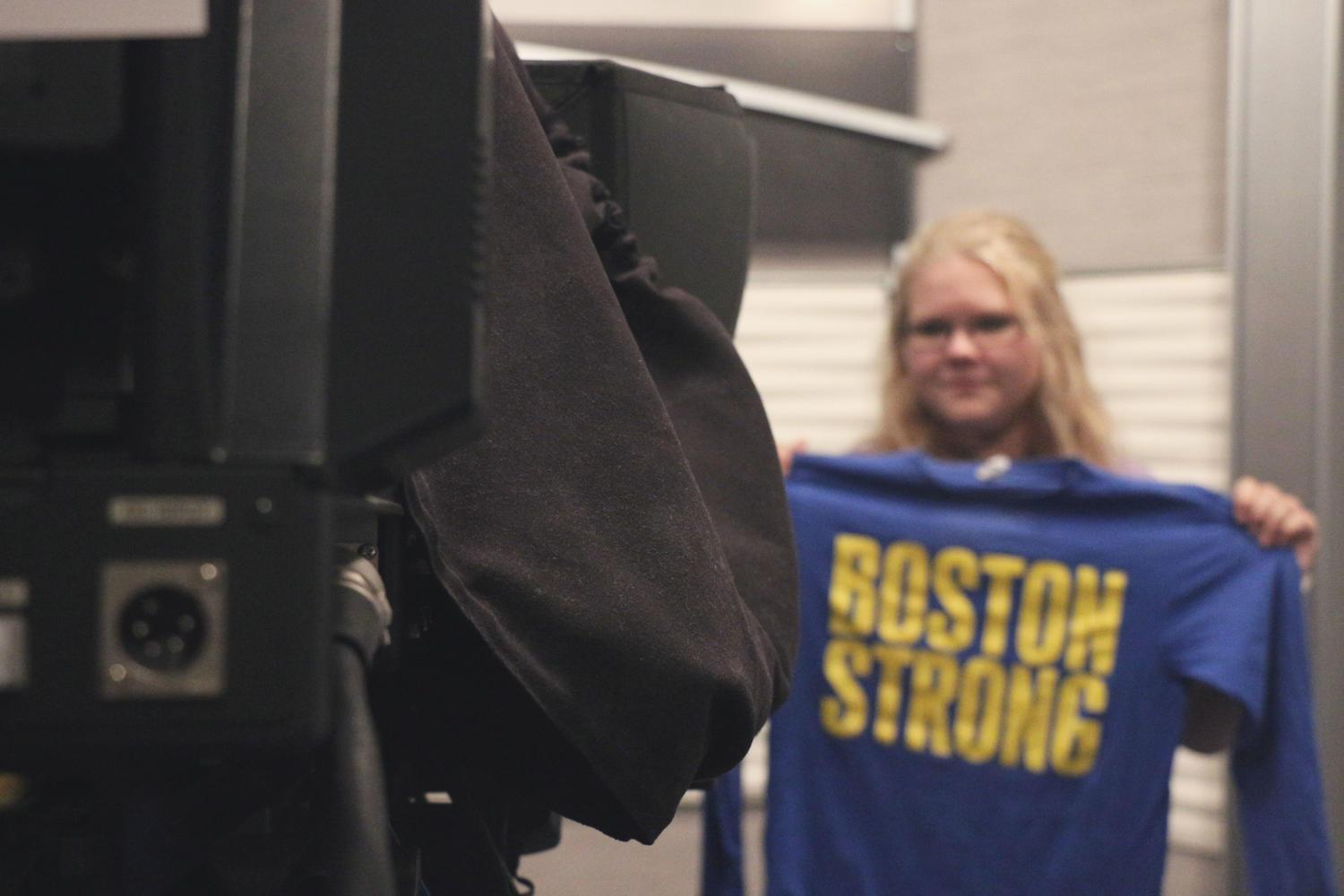 "Sophomore Annie Rose looks into the lens of a film camera, representing her Boston nativity with a ""Boston Strong"" shirt. Rose moved from Boston as a child and said she remembers the impact of the Boston Marathon on her family after moving to Indiana."