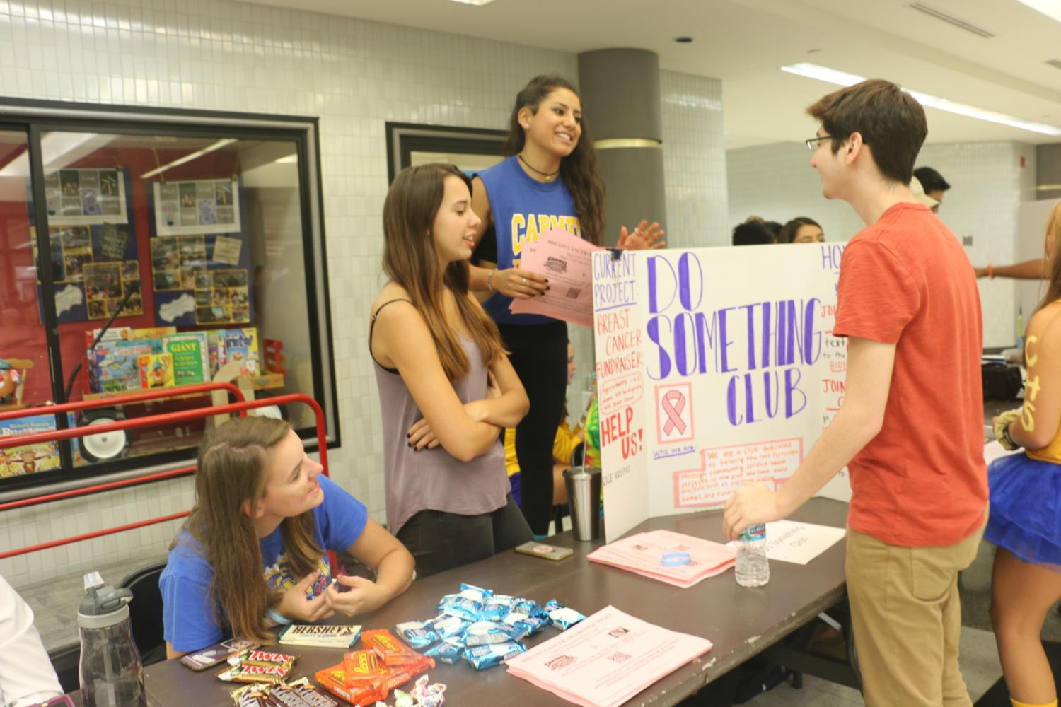 """Juniors Samantha """"Sammi"""" Kadinger, Ula Miller and Dulce Crane of the Do Something Club explain their club to junior Adrian Castaneda. The Do Something Club meets every two weeks on Tuesdays in E212. Currently, the Do Something Club has taken on a project to help support breast cancer."""