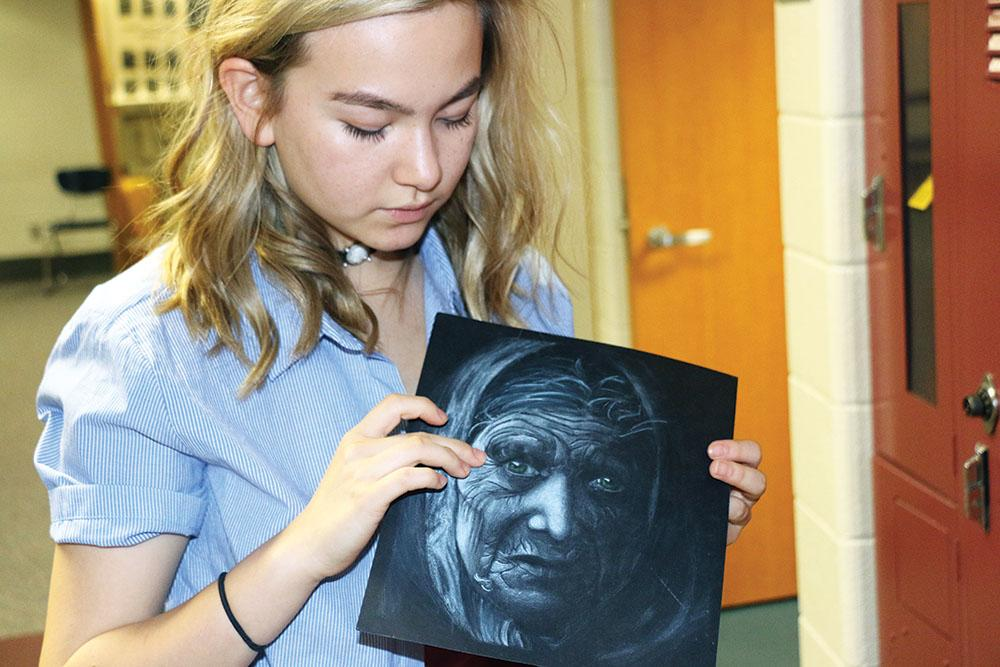 Junior Adelle Murphy presents her favorite piece of artwork. The old woman has green eyes that contrasts with the rest of the drawing in black and white in order to showcase that her eyes are not dull due to time; they are still bright. Murphy said female artists are still not as represented and not taken seriously.