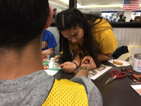 Mayil Bhat, Kenya Club member and junior, applies henna ink on a CHS student to raise money at the Kenya Club Homecoming booth. Mandeep Dhillon, Kenya Club president and junior, said the club will continue fundraise in the future to support the education of Kenyan orphans.
