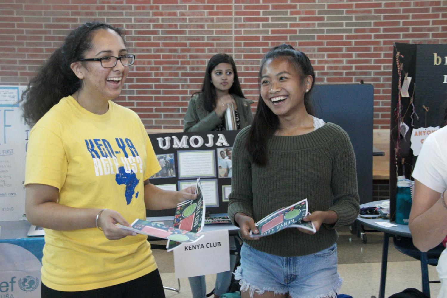 At the activities fair, Mandeep Dhillon, Kenya Club president and junior (left), and Rene Pin, Kenya Club member and junior (right), pass out Kenya Club flyers. Dhillon said one of her goals for Kenya Club this year is to gain new members and expand the club within CHS.