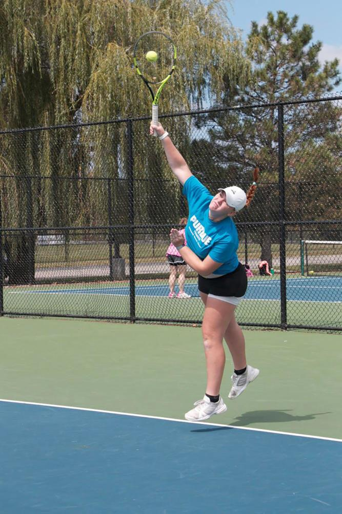 Senior Kiersten Carlson warms up her serve during a practice. Carlson said she did online school for a semester to pursue tennis more seriously.