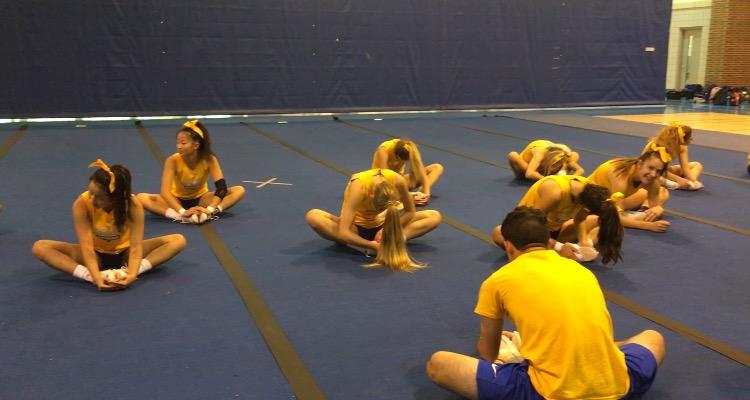 The cheerleading team warm up with static before an afternoon practice. A normal practice consists of dynamic and static stretching, and team and individual skills.