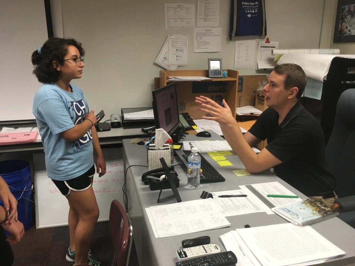 Do Something Club sponsor James Ziegler discusses the club's upcoming breast cancer research fundraiser with freshman Setareh Hamidi. Ziegler said the majority of the fundraising for the Breast Cancer Research Foundation will happen on Oct. 6 at the home football game.