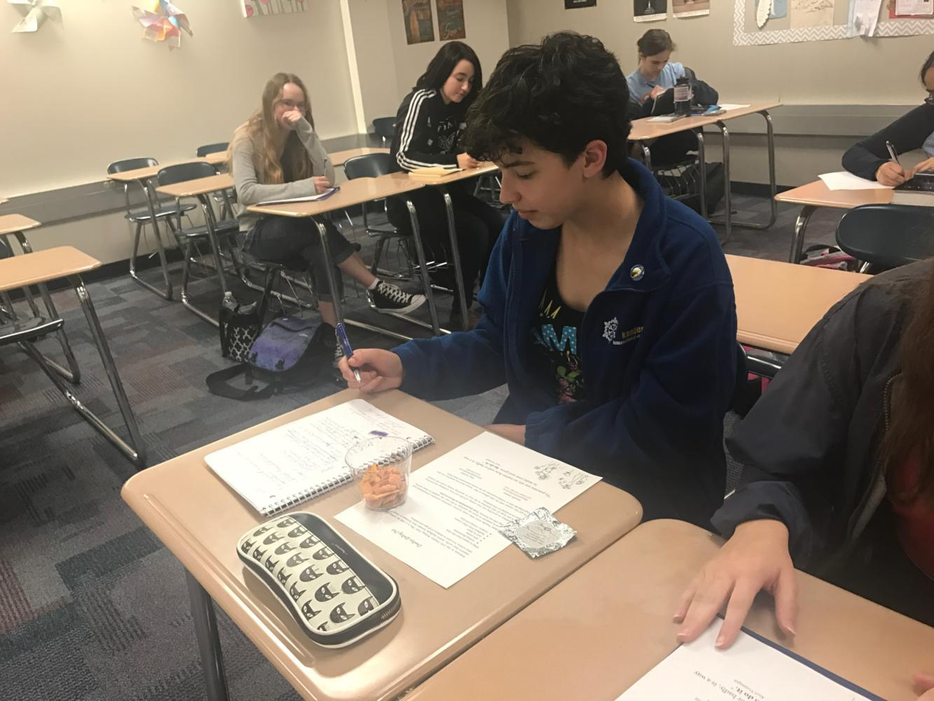 Creative Writing Club member Mackenzie Gonzales begins writing her warm up writing piece of the day. While doing so, she enjoys one of her favorite writing snacks: goldfish.