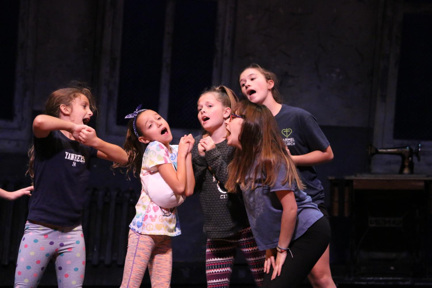 """Freshman Emily Chrzanowski, second from the right, rehearses a number from the Booth Tarkington Civic Theatre's production of """"Annie"""" as an orphan. As a freshman, Chrzanowski has to manage her first year of high school with hours of rehearsal each week."""