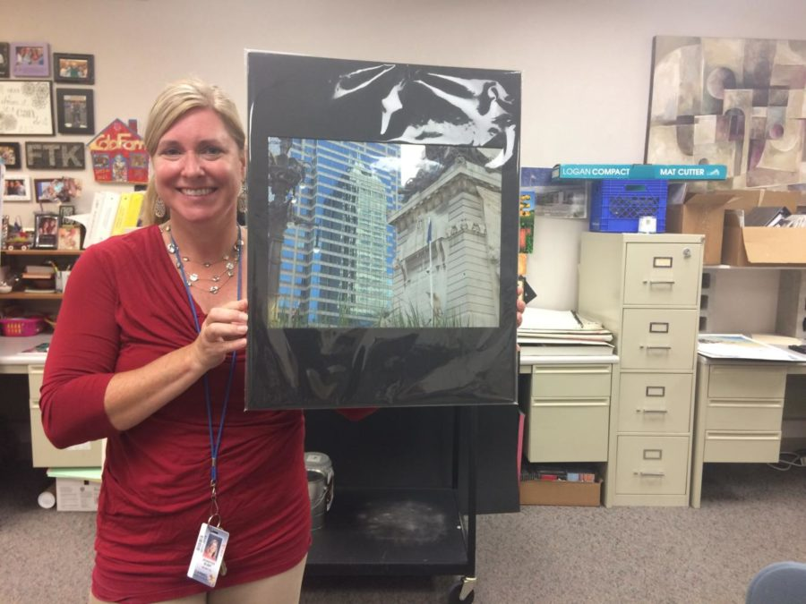 Art Club sponsor Jennifer Bubp holds up a painting that will be used at the club's silent art auction. Art students turned in some of their works to be displayed at the auction, which will take place throughout the school day on Oct. 17.