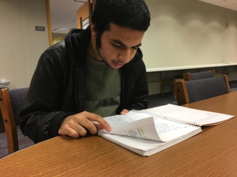 "Co-president and junior Danial Tajwer looks over notes for the upcoming conference. Tajwer said, ""We are going to start writing position papers for that (the conference) very soon."""
