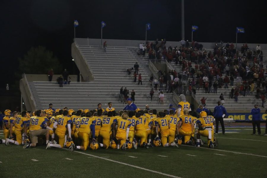The football team huddles before the game starts. Schumann said he playing for the team brings a sense of brotherhood.