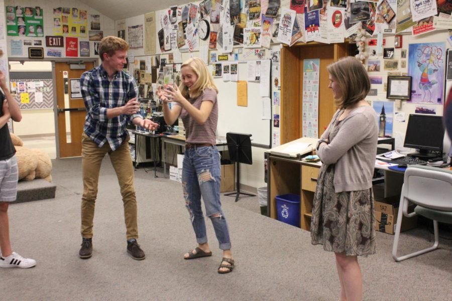 Shawn Horrocks and Piper Dafforn, ComedySportz members and juniors, pretend to hold a puppy during a ComedySportz rehearsal. This exercise was part of a game designed to improve the team's ability to portray physicality.