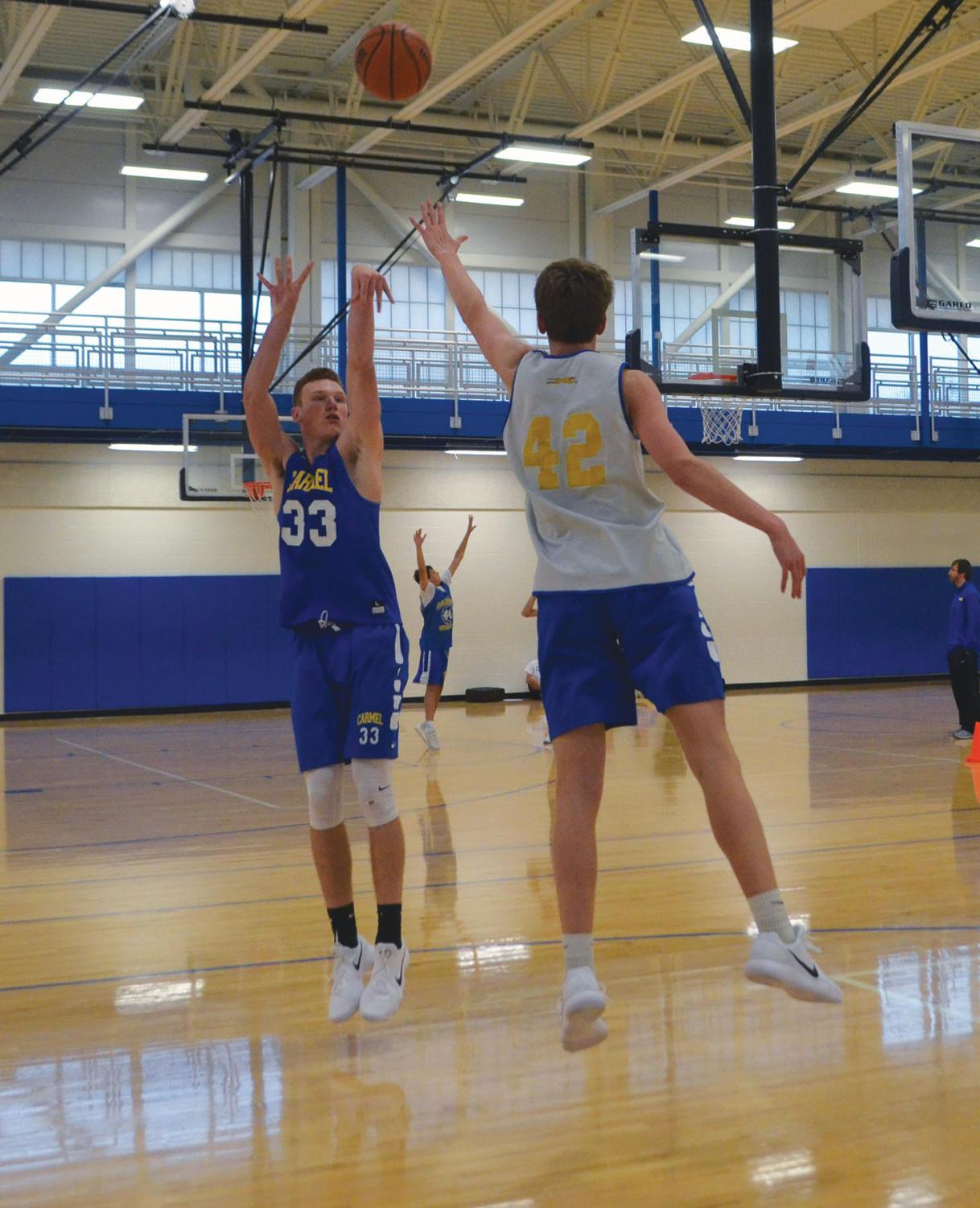 John-Michael Mulloy, varsity basketball player and junior, shoots over junior Benjamin Frische during practice. Mulloy said he only tweets things that help maintain a positive image. AGRAYAN GUPTA | Photo