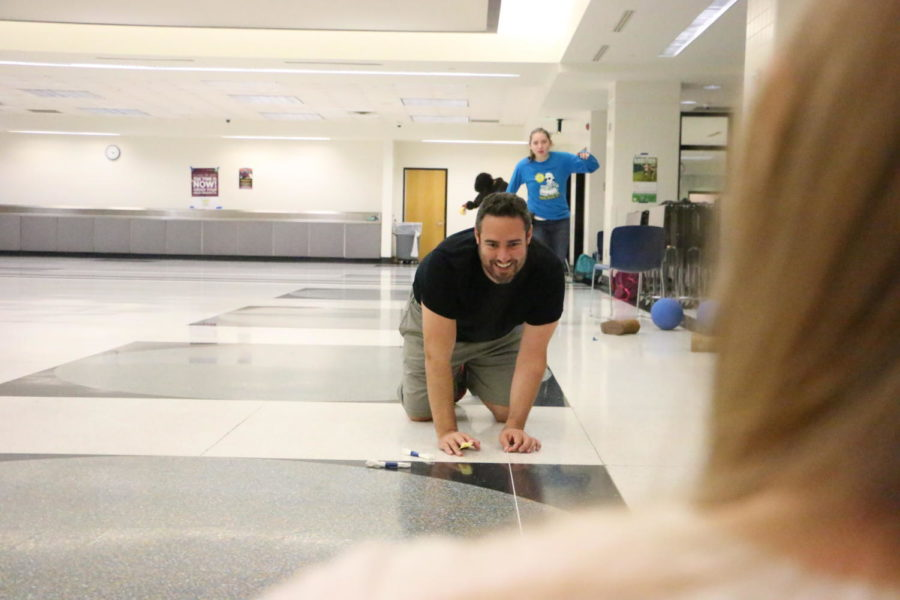 Goalball Club sponsor Dave Romano tapes down a temporary court before the club members start playing. Sanchez said they will play in the main cafeteria after school whenever club members are available.
