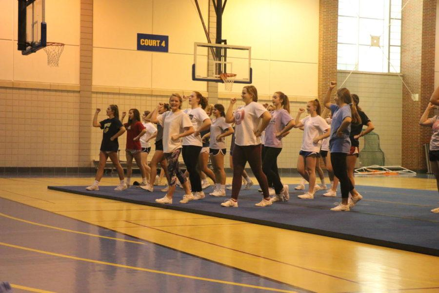 Winter Cheerleaders stand in their triangle formations as they learn a cheer. The team did the same cheer last year, and due to it's reaction they decided to use it again for games.
