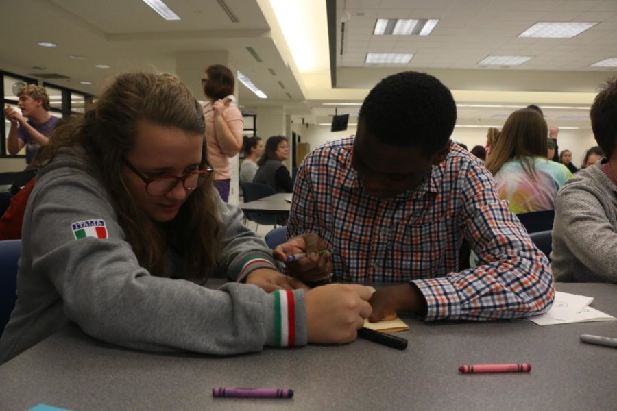 Senior Laurel Hulett works on a Christmas card with Orlando Robinson, her Best Buddy and sophomore, in the main cafeteria. Best Buddies have arranged small get-togethers and meetings in and out of school for students to interact with their Best Buddies.
