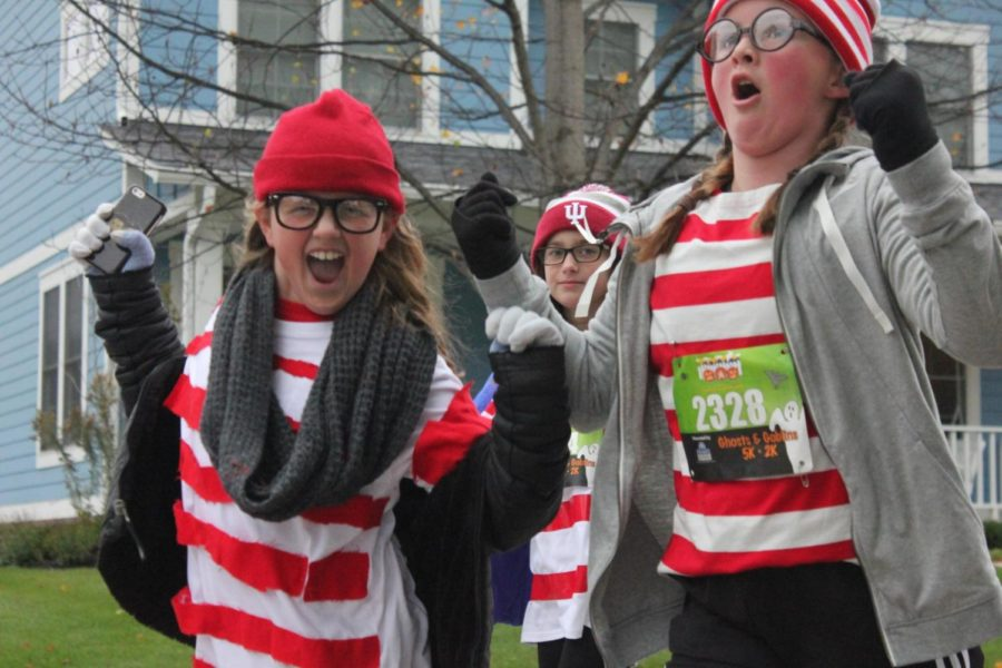 """Despite the frosty morning, two young runners smile and cheer for the race. The girls are dressed in matching Waldo outfits based off of the children's book """"Where's Waldo?"""""""