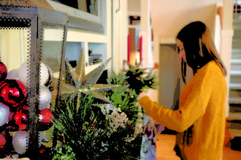 Sophomore Elle Nichol sets up miniature Christmas trees over her fireplace.  Nichol said she incorporates her German tradition with Christmas.
