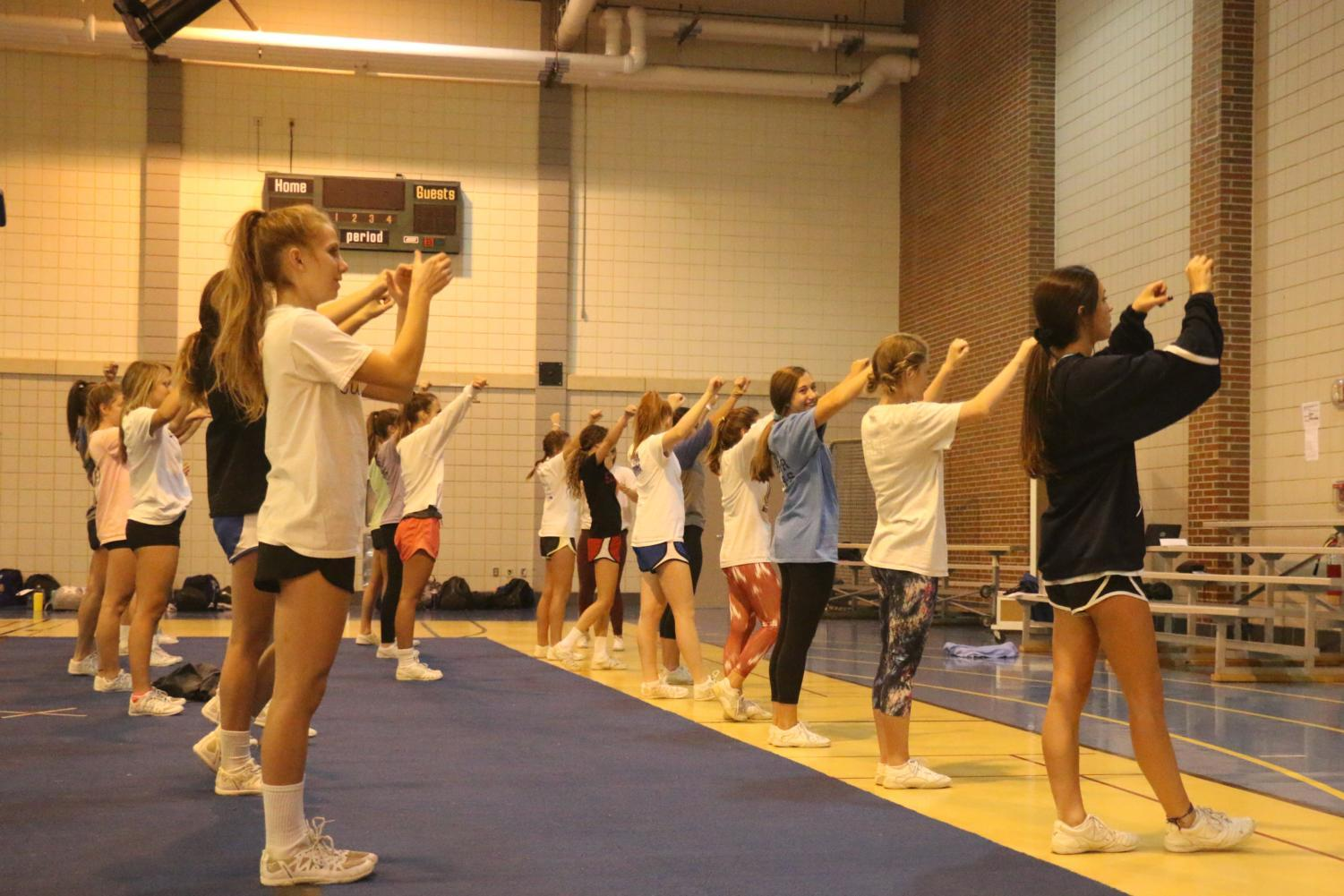 Winter Cheerleaders practice their cheers for basketball games. Blue and Gold cheer teams cheer for both boys and girls basketball, but they alternate which games they cheer so that the team isn't overwhelmed by the schedule.
