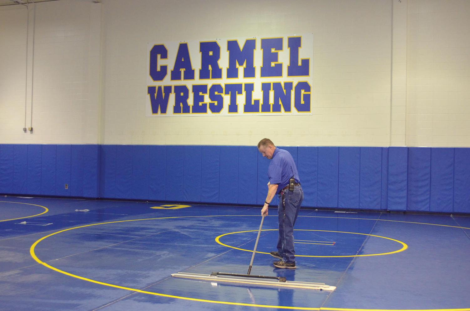 Custodian David Hays mops the wrestling mat. Hays said he sometime faces time constraints due to after-school activities.  Agrayan Gupta | Photo
