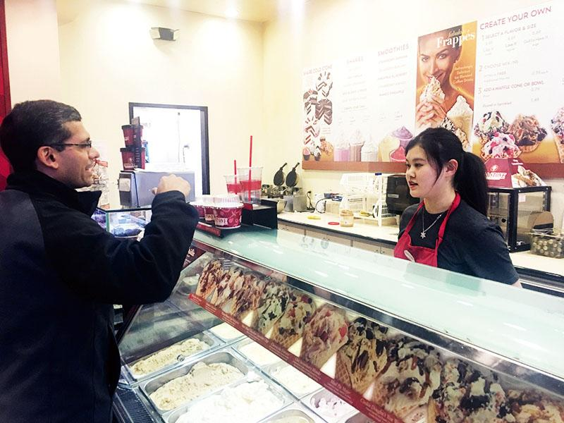 Junior Kelly Xiang takes an order at Cold Stone Creamery. According to Xiang, working over break gives her something to do productively, which allows her to feel more responsible.