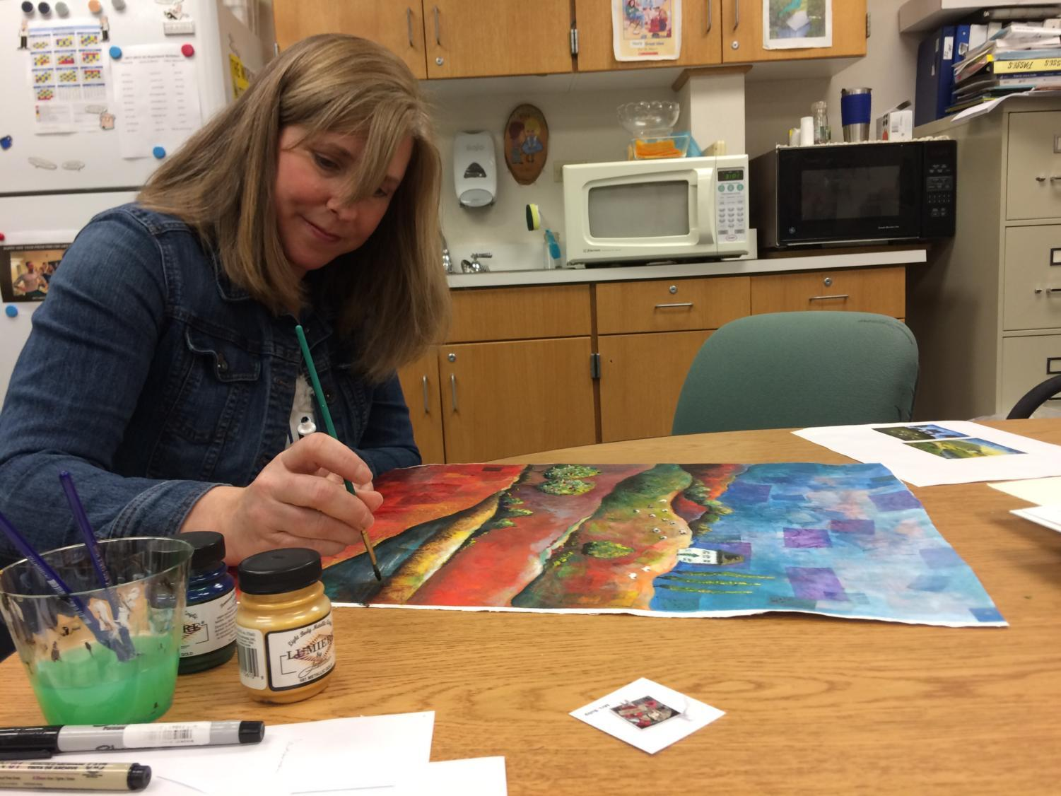 National Art Honor Society (NAHS) sponsor Jennifer Bubp finishes a painting for an art show at Soho Cafe, which took place on March 1. NAHS will host an event on March 29 to raise money for charity.