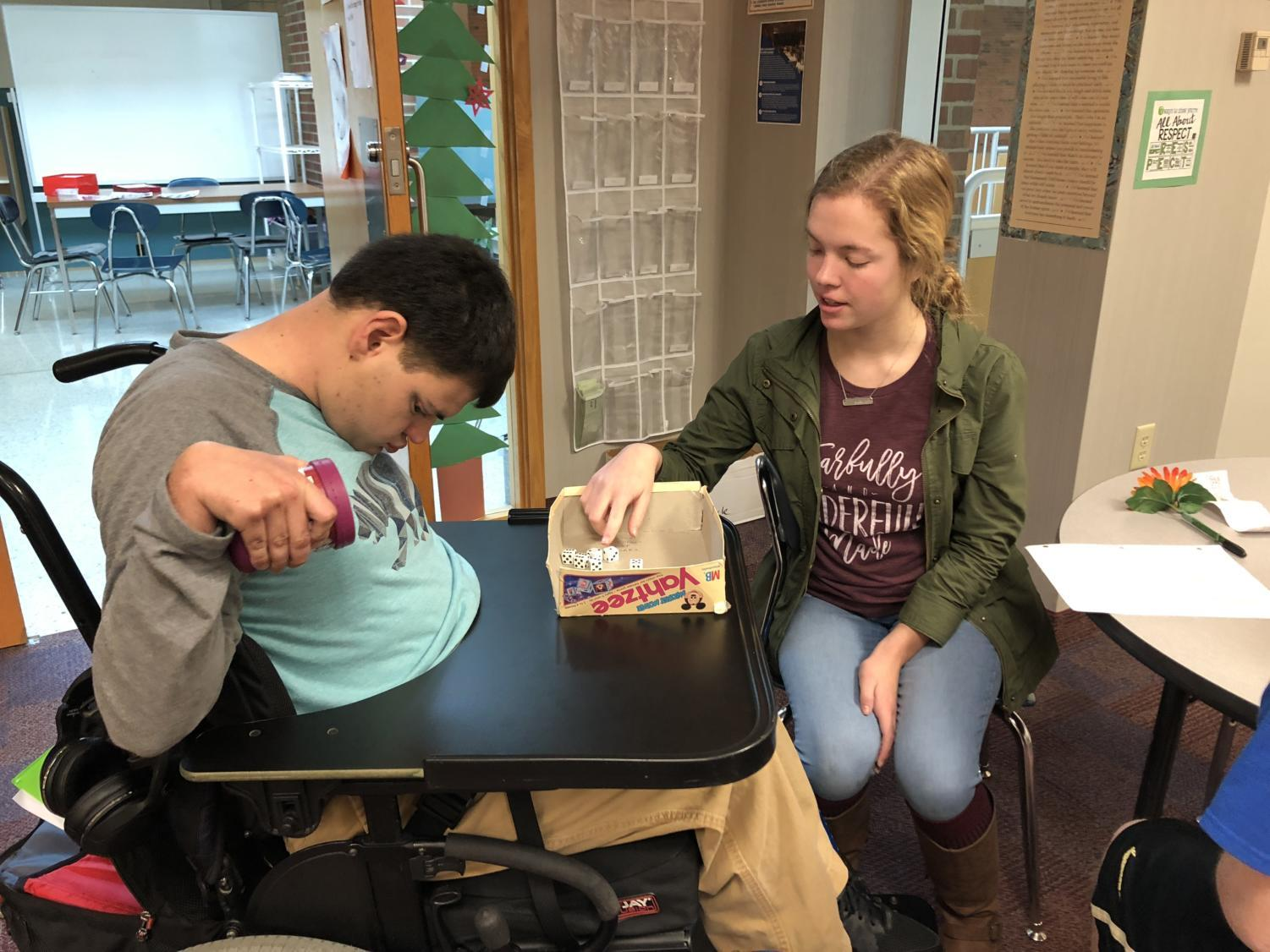 Best Buddies president Anne Schuh plays Yahtzee with a student with special needs. Anne spends her SRTs in D206, where she can spend time with peers with disabilities and aid Best Buddies sponsor Dana Lawrence.