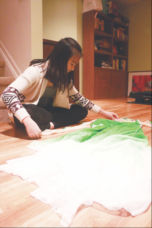 Freshman Melissa Su looks at her costume for a previous year's Indianapolis Chinese Community Center Inc. (ICCCI) performance. According to Su, these celebrations allow her to connect with her culture more.