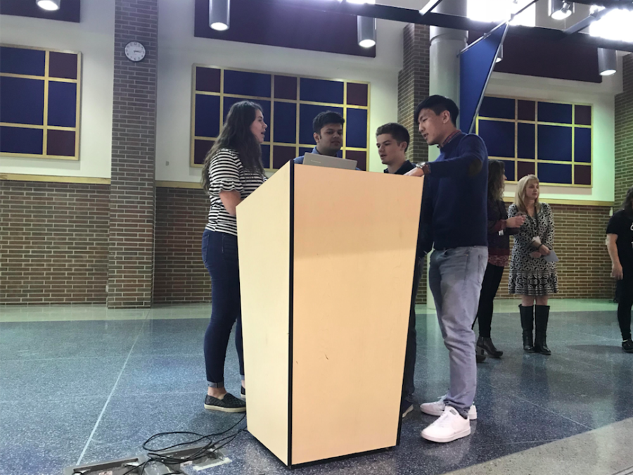 NHS officers Dalton Thompson, Jai Sanghani, Hannah Park and Justin Park stand around the podium and review the agenda before the monthly meeting begins. The officers announced the two shifts available for the CEF telethon and discussed group hour opportunities for carnation sales.