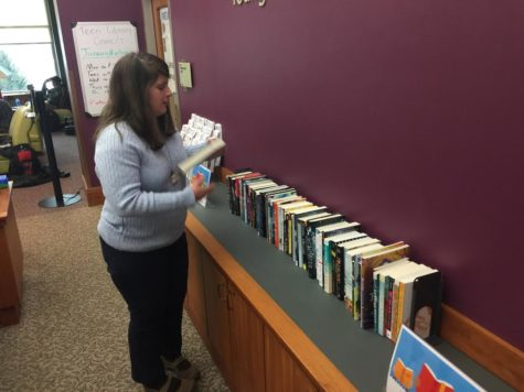 Jamie Beckman, young adult section librarian, arranges books, which are prizes of an upcoming winter reading program. This is the second year that the library will host a winter reading program.