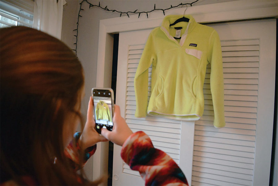 Junior Mea McCormack takes a picture of a Patagonia sweatshirt to sell on Instagram. McCormack said she only posts clothing that is in good condition.