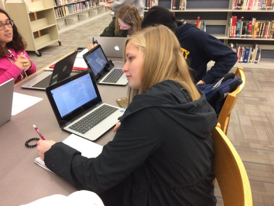 Lauren Roop, House member and senior, works on her homework during class to make time for House's most busy time of the year. She has been involved in House for several years and has witnessed this in the past.