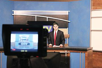Griffin Gonzalez, CHTV anchor, WHJE director and senior, looks at the camera before going on air. Gonzalez said he loves broadcasting because he wants to inform his audience of important news.