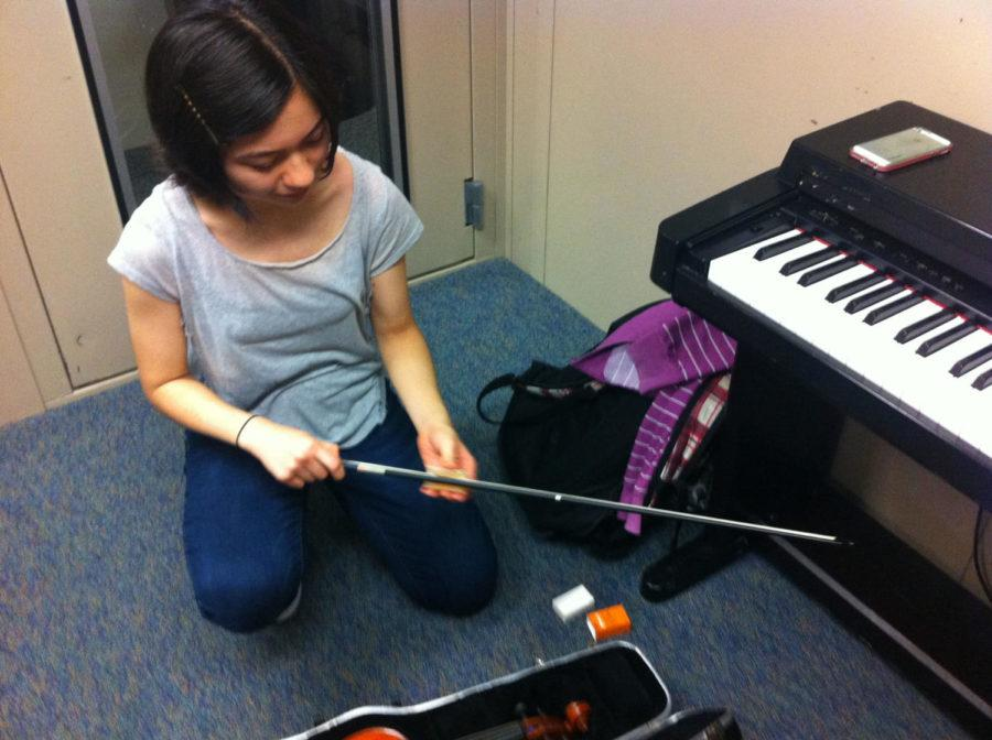 Anna Li-Harezlak, Share the Music vice president and senior, prepares her instrument. Li-Harezlak said participation in Share the Music could involve not only instruments but also singing and theatre.